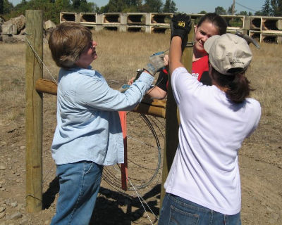 Women working with a fence brace