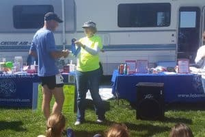 Photo of volunteer awarding blue ribbon to runner